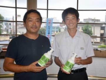 コラボ商品を手にする須山向陽さん(右)と販売会社の黒木靖之さん=鹿屋市役所