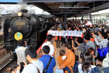 豪雨被災地を応援するヘッドマークを付けたSLの前で記念撮影をする鉄道ファンたち