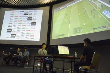 ステージ上で熱戦を繰り広げる出場者(手前2人)。プレー画面を見ながらプロプレーヤーらが実況、解説した(左奥)