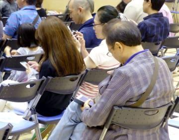 AIを活用した防災訓練で、スマートフォンで被災情報を入力する参加者=29日、東京都江東区
