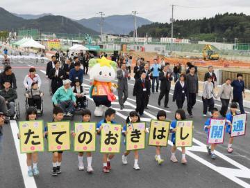 館の沖橋の開通を祝い、渡り初めをする子どもたちと関係者ら=29日、陸前高田市高田町