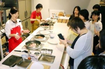 新潟県産の新米に合うおかずを調理する佐藤智香子さん(左)=29日、新潟市中央区