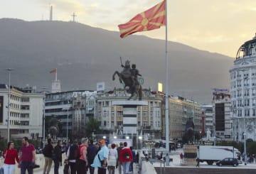 マケドニアの首都スコピエ中心部の広場に掲げられた国旗と、古代マケドニアのアレキサンダー大王を模したとされる像=9月29日(共同)