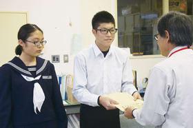 義援金を手渡す大滝中生徒会会長の磯野さん(中央)と副会長の三浦さん(左)
