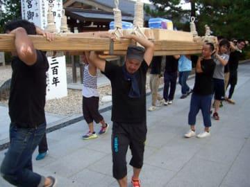 大神輿の大きさに組んだ担ぎ棒を肩に乗せ、巡行の練習をする実行委のメンバーたち(京都府宮津市大垣)