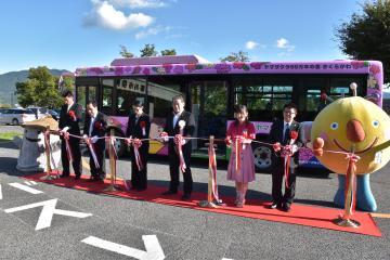 真新しいラッピングバスを前にテープカットを行う関係者=桜川市役所大和庁舎