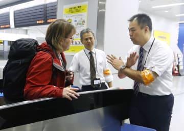 台風24号の接近で新幹線が計画運休し、JR新大阪駅の改札で外国人に対応する駅員=30日午後