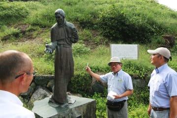 横瀬浦に上陸した宣教師、ルイス・フロイスの説明を受ける安部さん(中央)=横瀬浦公園