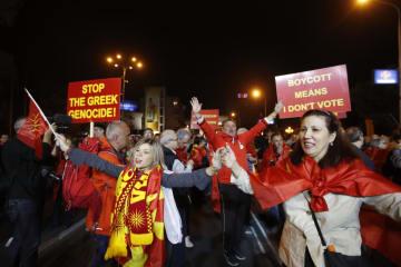 30日、マケドニアの首都スコピエで国民投票の低調な投票率が発表されて祝う人々(AP=共同)