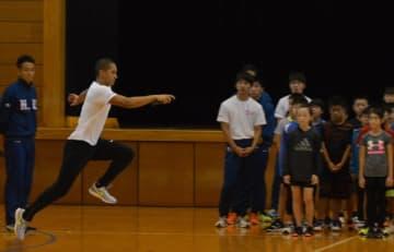 子どもたちに走り方の基本を指導する飛鳥選手(左から2人目)