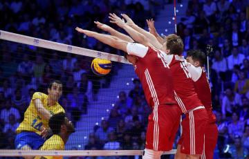 バレーボール男子の世界選手権決勝、ブラジルのソウザ(左)のスパイクをブロックするポーランド=30日、トリノ(ロイター=共同)