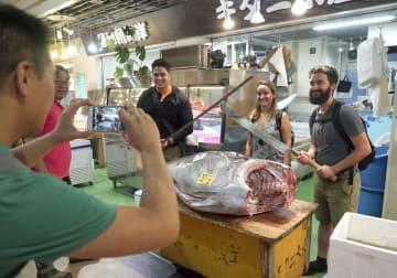 正式オープンした「築地魚河岸」の鮮魚店で記念撮影する観光客=1日午前、東京都中央区