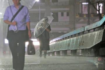 風雨が強まる中、傘を差して四条大橋を歩く人たち(30日午後6時38分、京都市下京区)
