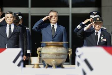 1日、ソウル近郊の空港で返還された韓国軍兵士の遺骨に敬礼する文在寅大統領(中央)(聯合=共同)