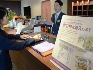 旅館の受付に掲示された宿泊税導入を知らせるポスター(1日午前9時40分、京都市中京区柳馬場通六角下ル・綿善旅館)