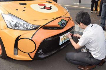 交付された愛媛版ナンバープレートを公用車に付ける県職員=1日午後、松山市森松町