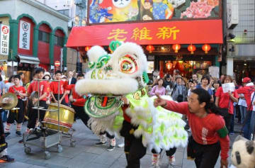 観光客が見守る中、鐘や太鼓のリズムに合わせ華麗な舞を披露する獅子=横浜中華街