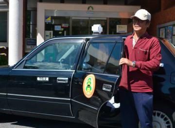 【乗合タクシーを利用した松尾さん=亀山市若山町の特定目的地停留所「図書館」で】