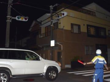 台風24号の影響で停電し、点灯しなくなった信号機と交通整理をする警察官=1日夜、静岡市