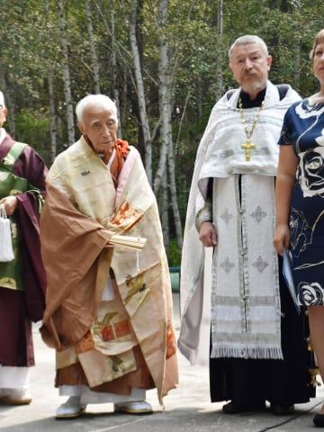 ロシア極東アムール州イワノフカ村で行われた慰霊祭に出席した僧侶の横山周導さん(左)=8月24日(共同)