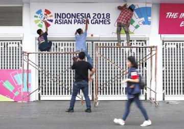 開会式が行われるブンカルノ競技場のゲートにアジアパラ大会の看板を取り付ける人たち=4日、ジャカルタ(共同)