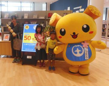 50万人目の来館者となり、土浦市のイメージキャラクター「つちまる」(右)と記念撮影する野口さん親子=同市立図書館