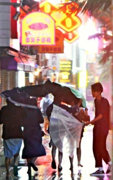 突風で傘を飛ばされそうになる国際通りの観光客=4日午後6時すぎ、那覇市牧志(田嶋正雄撮影)