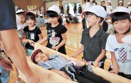 応急担架で負傷者を運ぶ訓練に取り組む児童たち=郡山市安積一小(写真は一部加工しています)