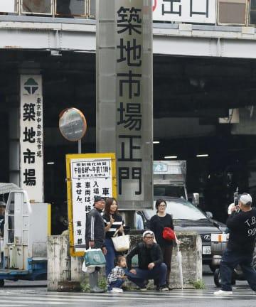 築地市場の最終営業日を前に、正門で記念撮影する人たち=5日午後、東京・築地
