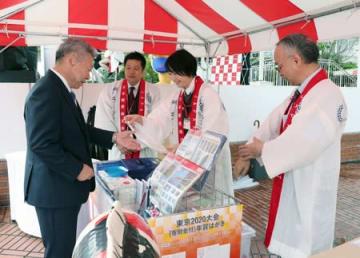 五輪のロゴマークが入った小千谷縮のはんてんを使った、日本郵便の年賀はがき発売記念イベント=1日、新潟市中央区