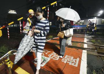 沿線火災の影響で止まった京浜東北線の列車から降りる乗客=5日夜、JR大森駅付近