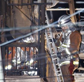 火災のあった住宅を調べる消防隊員=6日午前、大阪市平野区