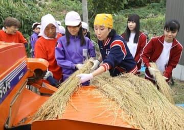 山古志の子どもたちと脱穀作業をする小林幸子さんら=5日、長岡市山古志虫亀