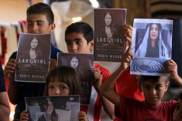 ナディア・ムラド氏の写真を掲げるヤジド教徒の子どもたち=5日、イラク北部ドホーク(ロイター=共同)