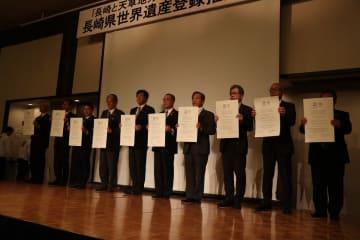 世界遺産登録認定書のレプリカを披露する自治体の首長ら=長崎市大黒町、ホテルニュー長崎