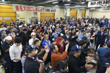 東京・築地市場の最終営業日を迎え、生マグロの競り場で一本締めをする仲卸業者ら=6日午前5時16分