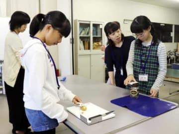 患者を支援するための調理道具を試す中学生