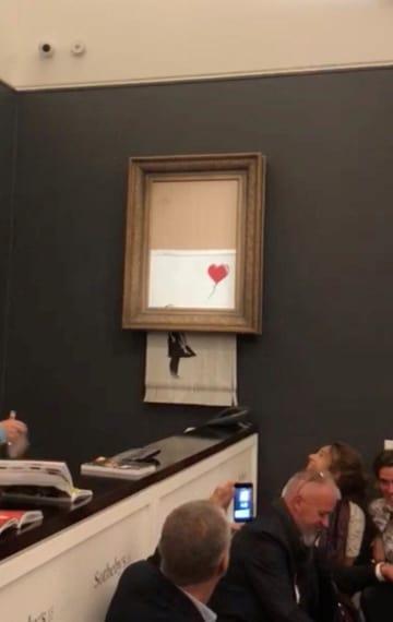 5日、ロンドンでの競売で落札直後に細断された正体不明の路上芸術家バンクシーの作品。ソーシャルメディアの動画から(INSTAGRAM/@PIERREKOUKJIAN/INSTAGRAM/@SINCEFINEART提供、ロイター=共同)