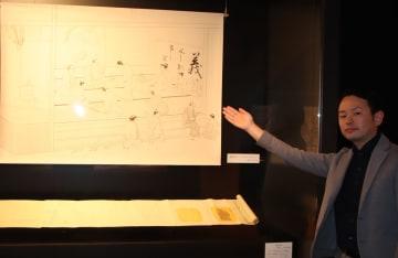 絵踏みを描いたパネルを紹介する出口学芸員=平戸市、平戸オランダ商館