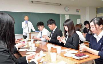 一戸オーナーパティシエ(左奥)の前でスイーツを試食する生徒たち