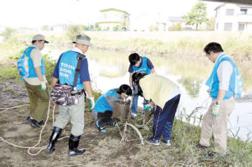 川から自転車を引き上げた参加者=6日、埼玉県草加市