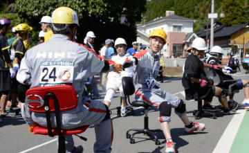 事務椅子に乗ってリレーする「いす-1グランプリ」の出場者=南関町