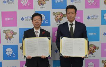 災害時の連携協定を結んだ水戸市の高橋靖市長(左)とOLSの大蔵勇人社長=同市中央