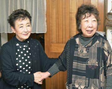 握手する加藤登紀子さん(左)と杉井紀子さん=9日午後、北海道厚真町