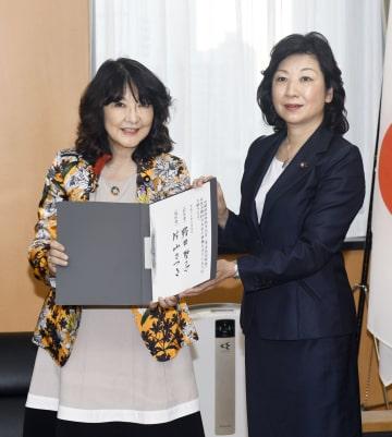 前任の野田聖子氏(右)から引き継ぎを受ける片山女性活躍相=9日午後、内閣府