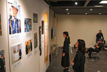 翁長雄志さんが影響を受けた父助静さんの琉歌などの展示に見入る来場者=9日、那覇市久茂地・タイムスギャラリー