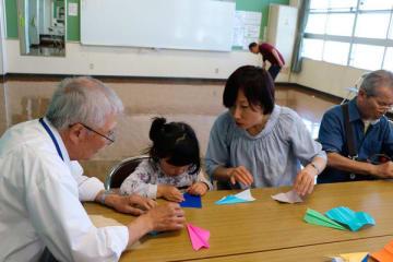 【メンバー(左)に教わって紙飛行機を折る親子ら=四日市市蔵町のなやプラザで】