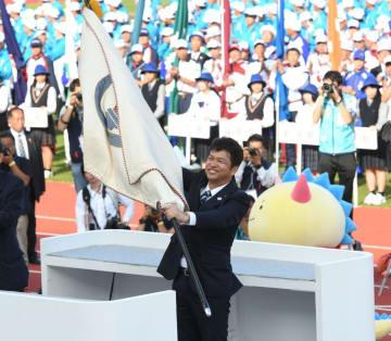 総合閉会式で福井県の西川一誠知事(左)から国体旗を引き継ぐ大井川和彦知事=福井市の福井県営陸上競技場