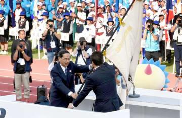 大井川和彦茨城県知事(右)に大会旗を笑顔で手渡す西川一誠知事=10月9日、福井県福井市の9・98スタジアム