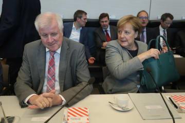 ドイツ南部バイエルン州の州議会選を前に、与党の会議に参加するメルケル首相(右)とゼーホーファー内相=9日、ベルリン(ゲッティ=共同)